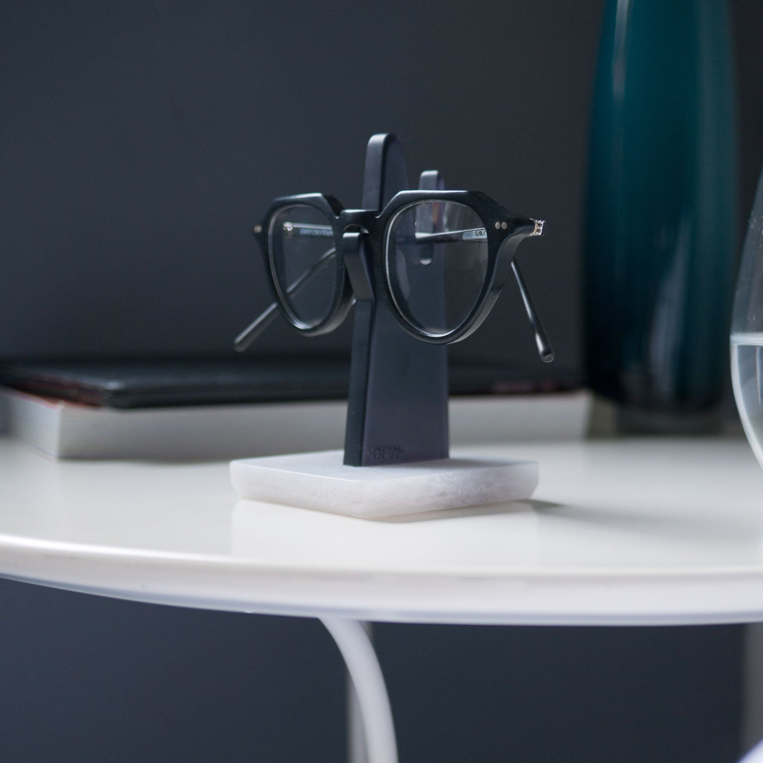Black oval glasses resting on grey spectacle stand