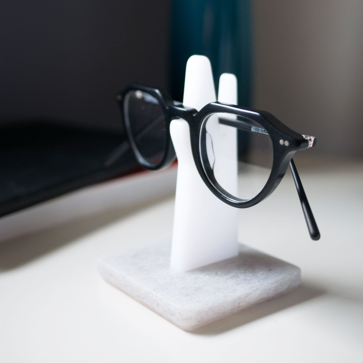 Black oval glasses resting on spectacle holder