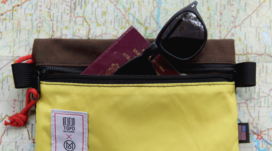 Black polarised sunglasses and British passport sticking out a yellow travel purse upon a map