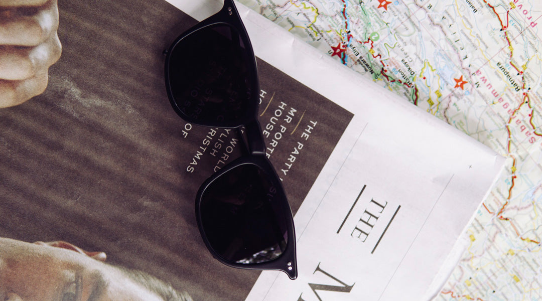 Black polarised sunglasses on top of newspaper and map