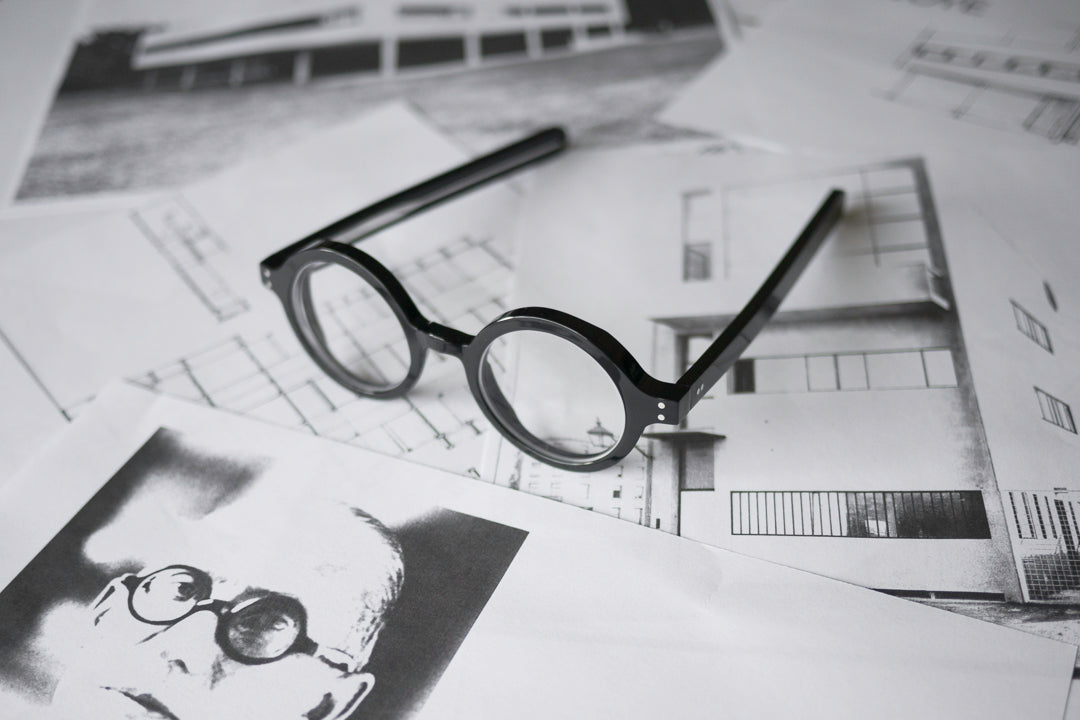 Black round Le Corbusier glasses on top of printed photographs