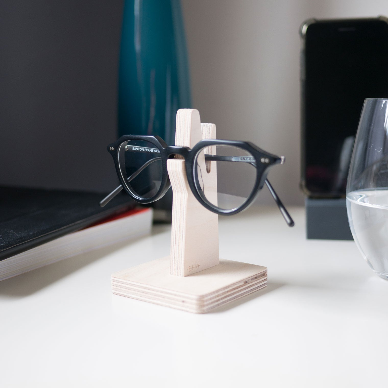 Black spectacles resting on wooden glasses holder