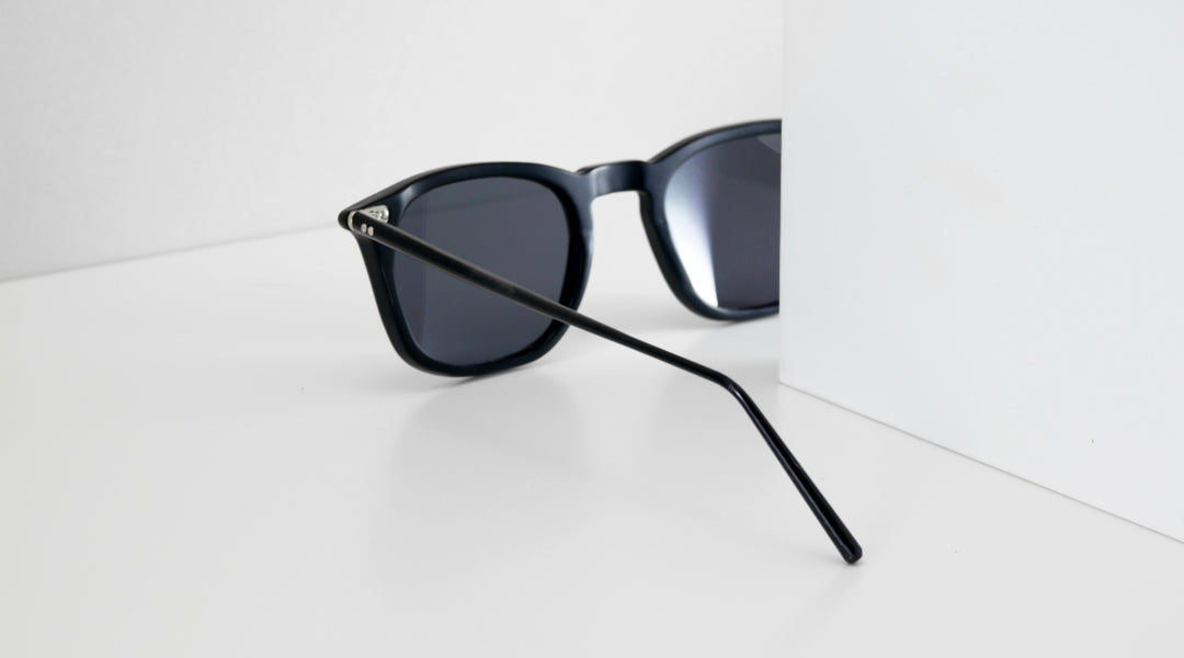 Black sunglasses facing towards white background with reflections on it's lenses