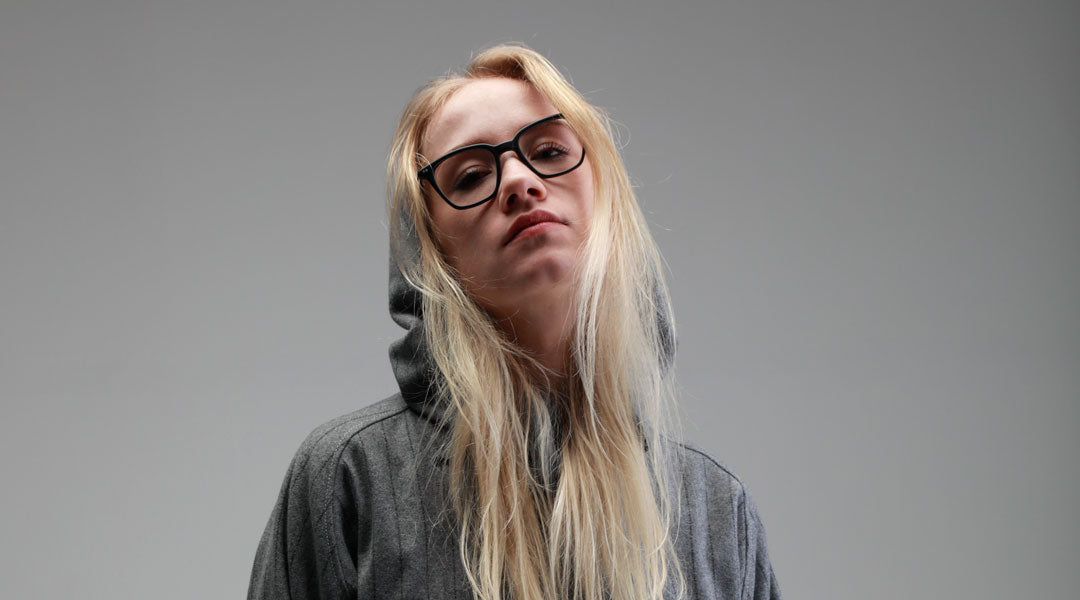 Blonde female wearing black rectangular glasses frame in a grey hoodie
