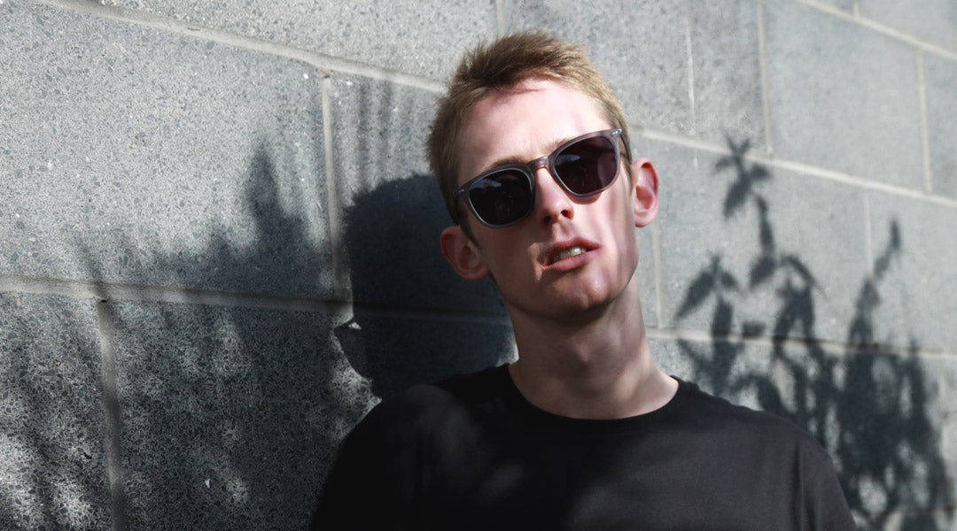 Blonde haired male wearing grey polarised sunglasses and black Tshirt in front of grey wall
