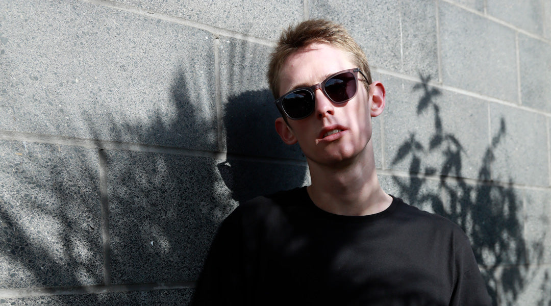 Blonde man wearing grey polarised sunglasses and black Tshirt on bright sunny day