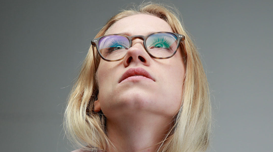 Blonde woman wearing tortoise anti glare glasses looking upwards