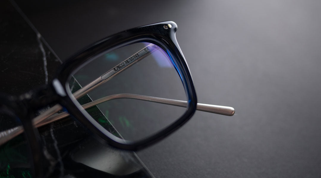 Blue spectacle frame with silver arms with colourful reflections on lenses