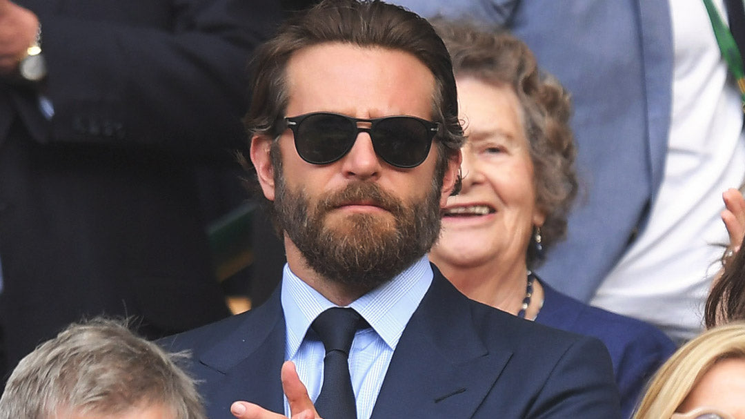 Bradley Cooper clapping at Wimbledon wearing blue suit and sunglasses
