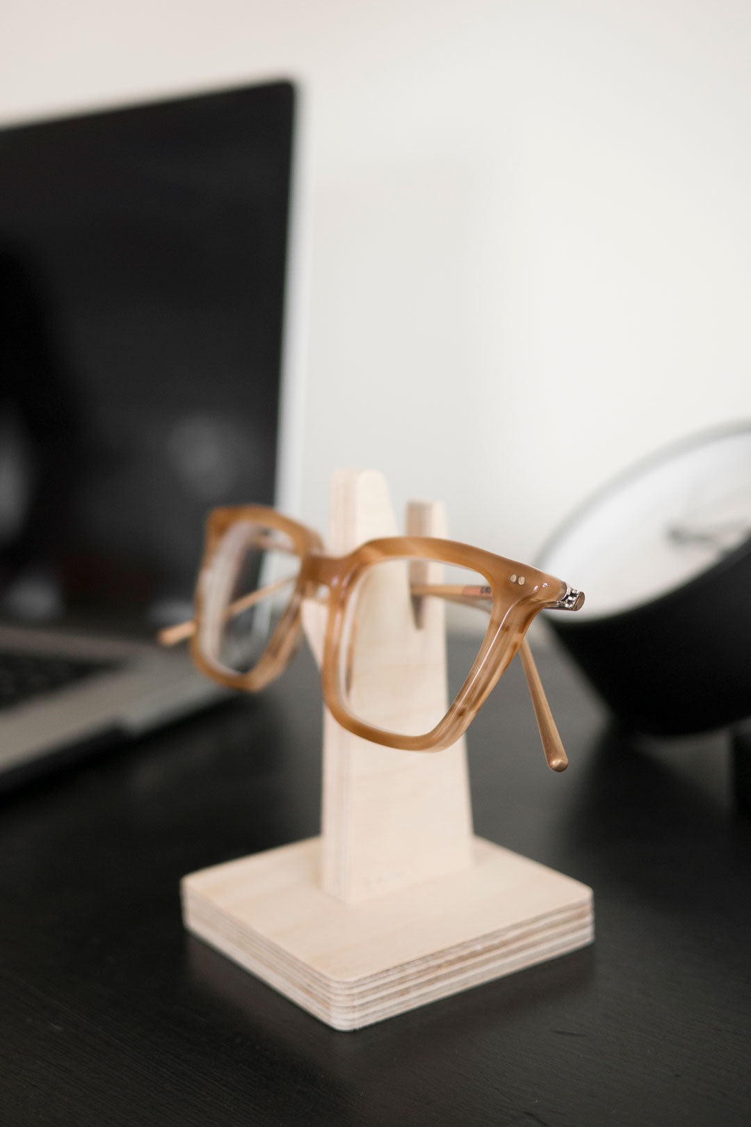 Brown glasses on wooden spectacle holder on workdesk