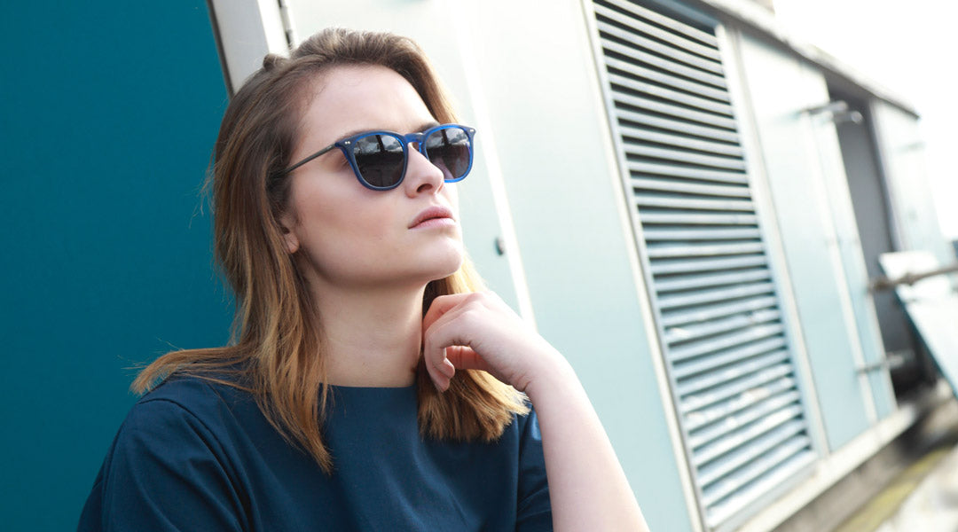 Brunette female sitting on a roof wearing blue polarised sunglasses