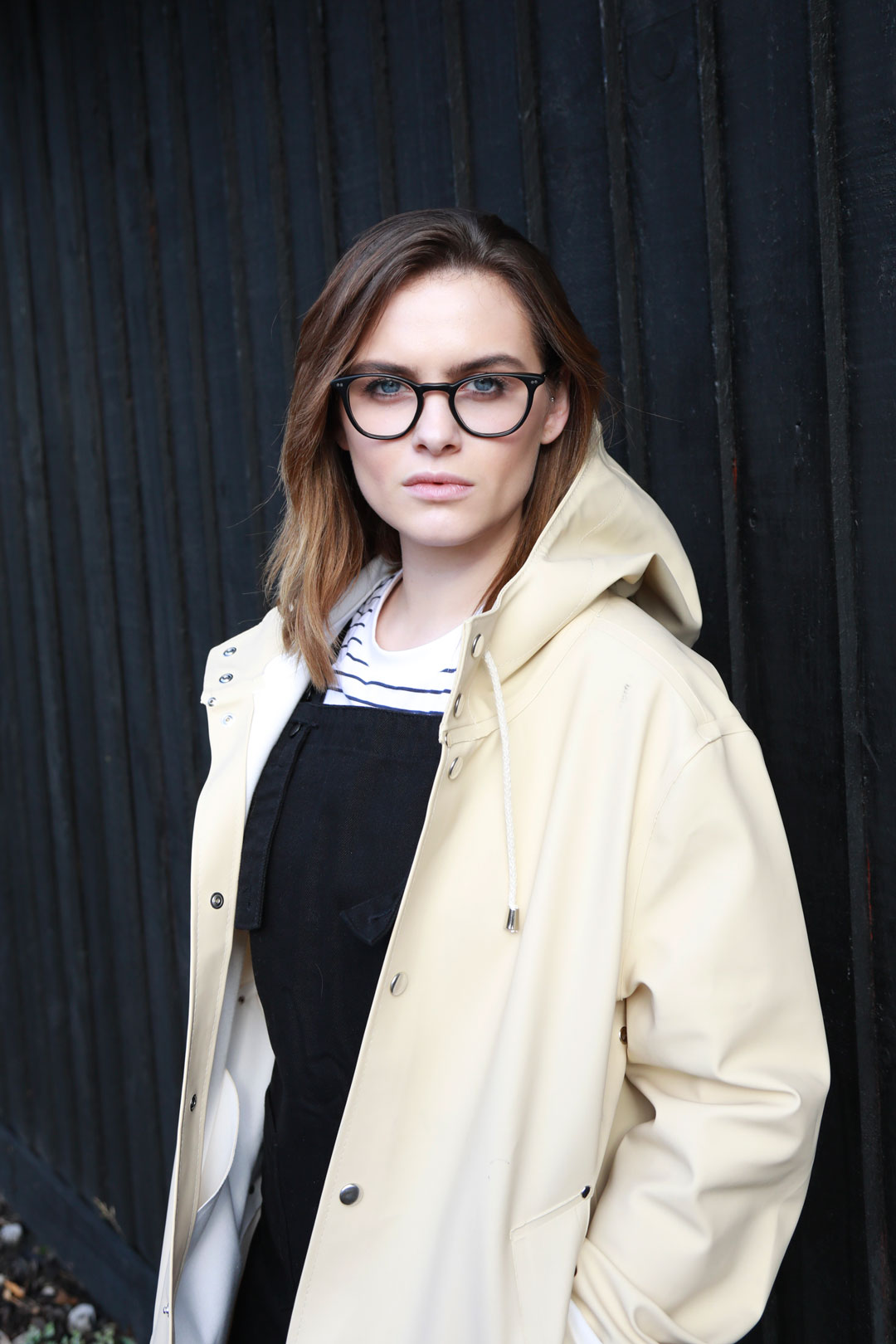 Brunette female wearing black glasses frame and beige raincoat in front of black wall