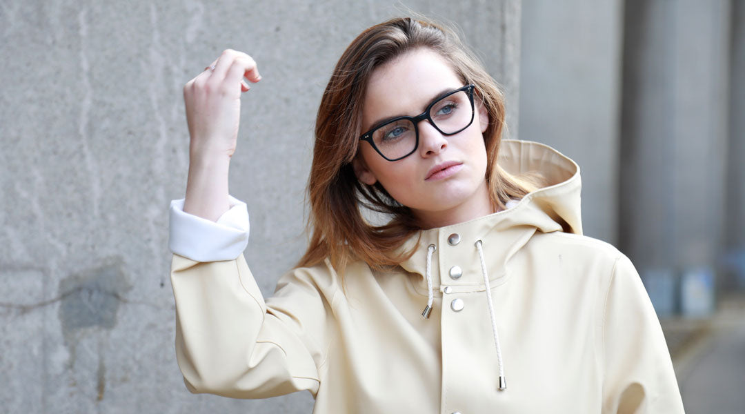 Brunette women wearing cream Stutterheim jacket and square black glasses