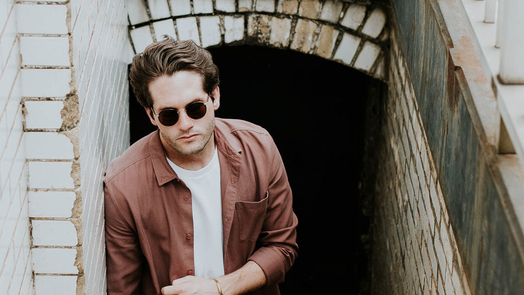 Caucasian male in large round sunglasses going up stairs