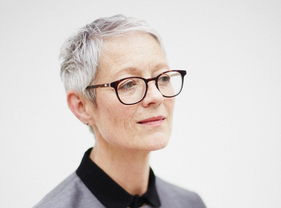 Caucasian women with very short grey hair wearing tortoise speckled glasses frame