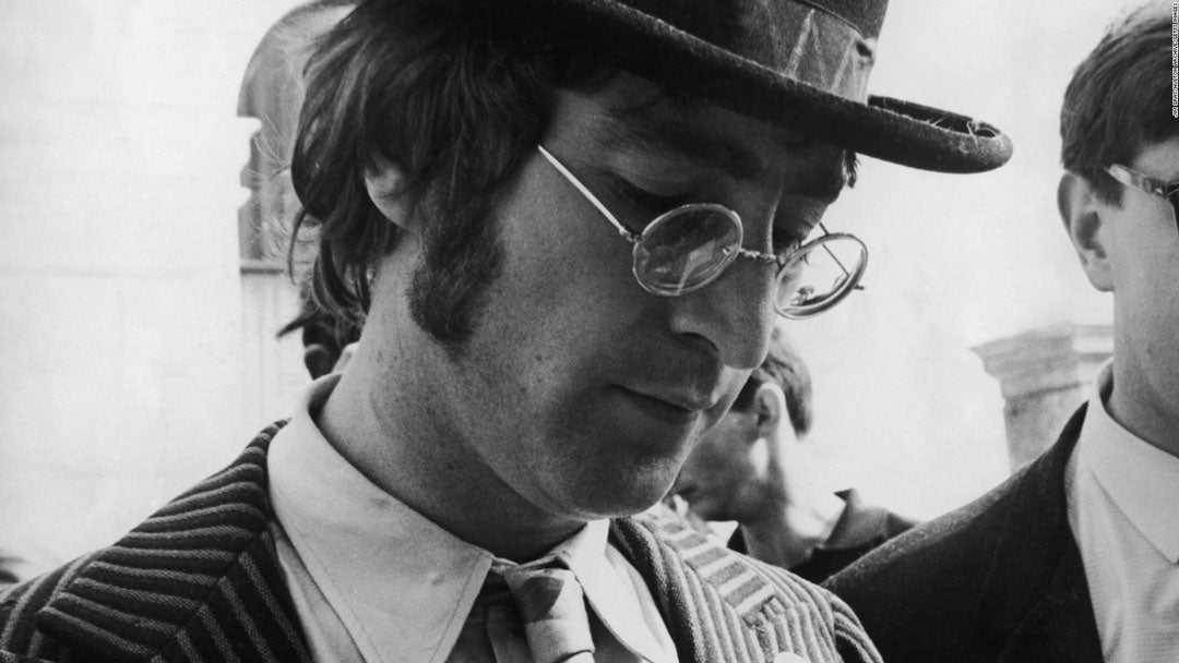 Close three quarter view of John Lennon wearing pin striped suit hat and roun rim spectacles