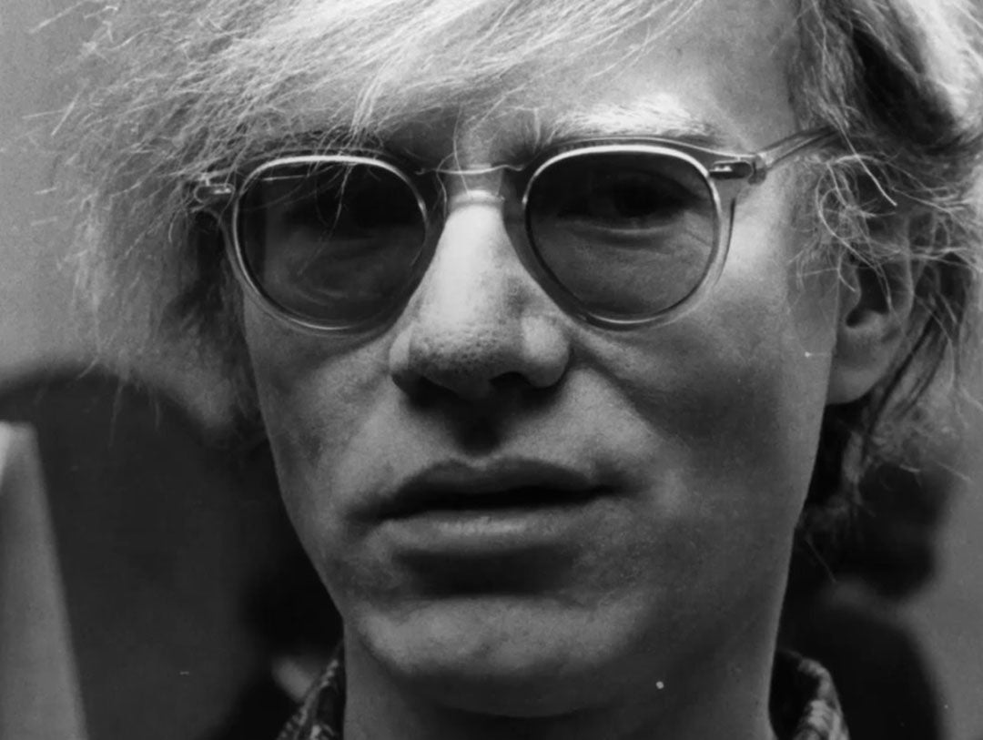 Close view of Andy Warhol wearing clear acetate sunglasses