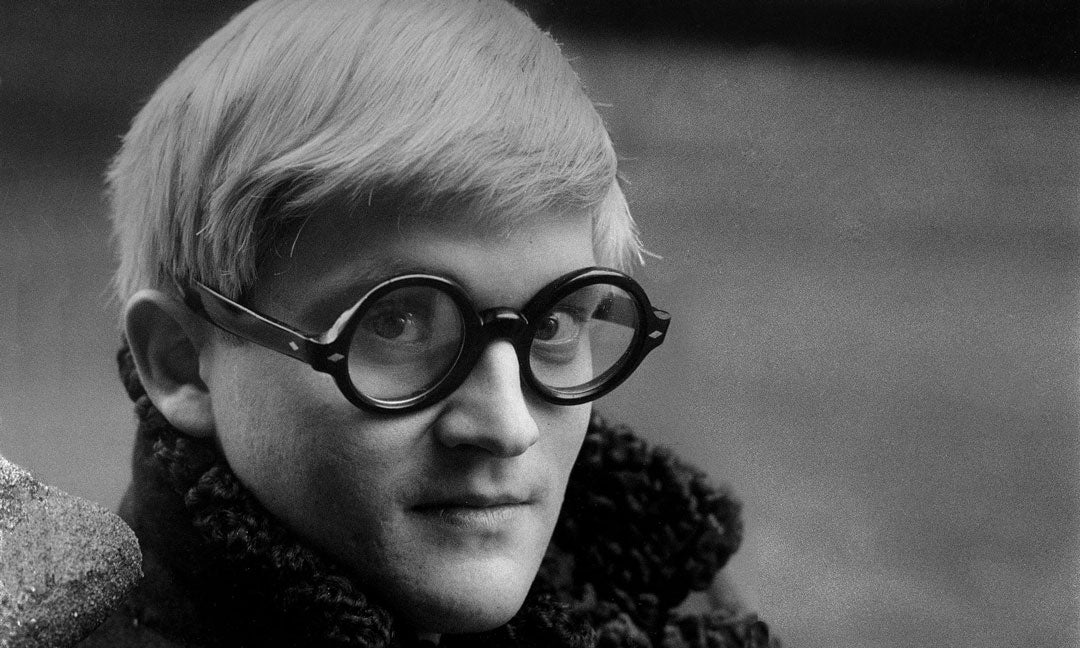 Close view of David Hockney wearing very thick round eyeglasses