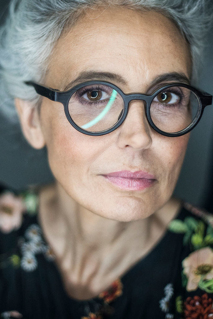Close view of grey haired lady wearing thick round glasses frame and a floral blouse