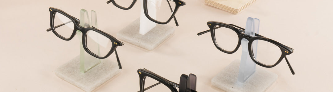 Collection of black glasses frames resting on eyeglass holders