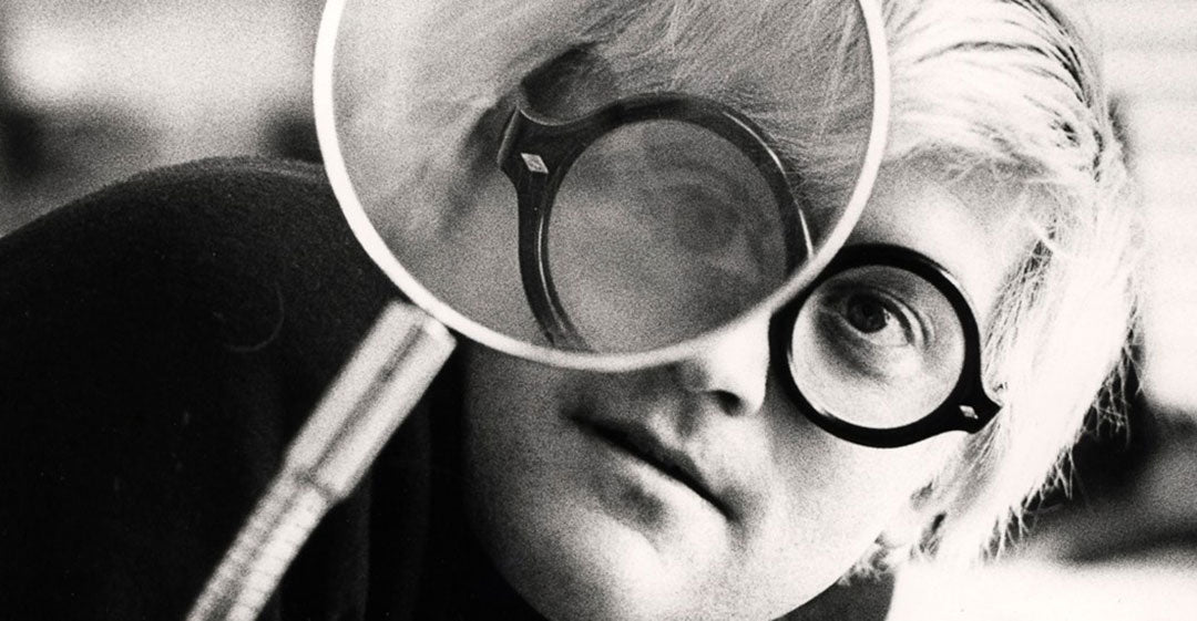 David Hockney looking through a magnifying glass wearing thick black glasses