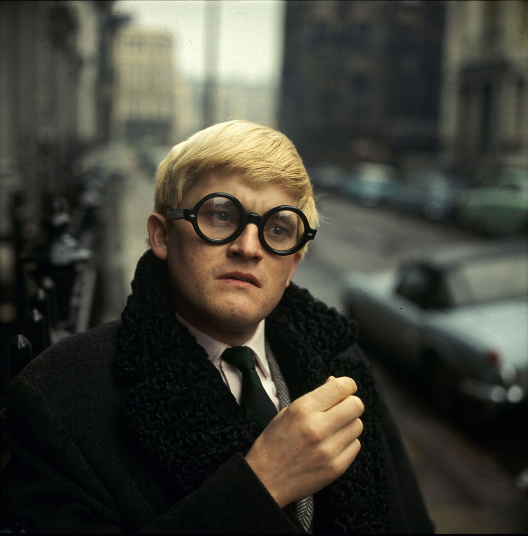 David Hockney standing in street wearing a formal coat and thick round glasses