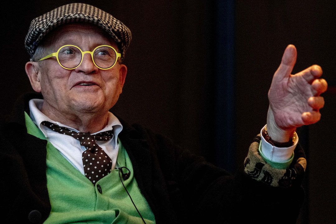 David Hockney wearing bright yellow glasses and green suit