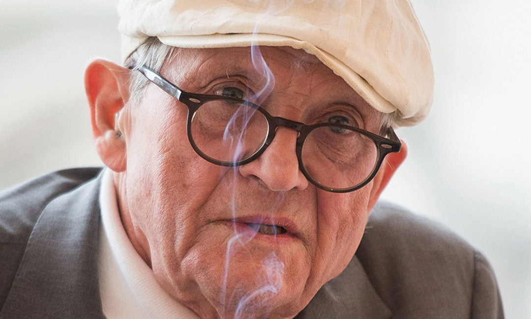 David Hockney wearing his white flat cap and round black spectacles