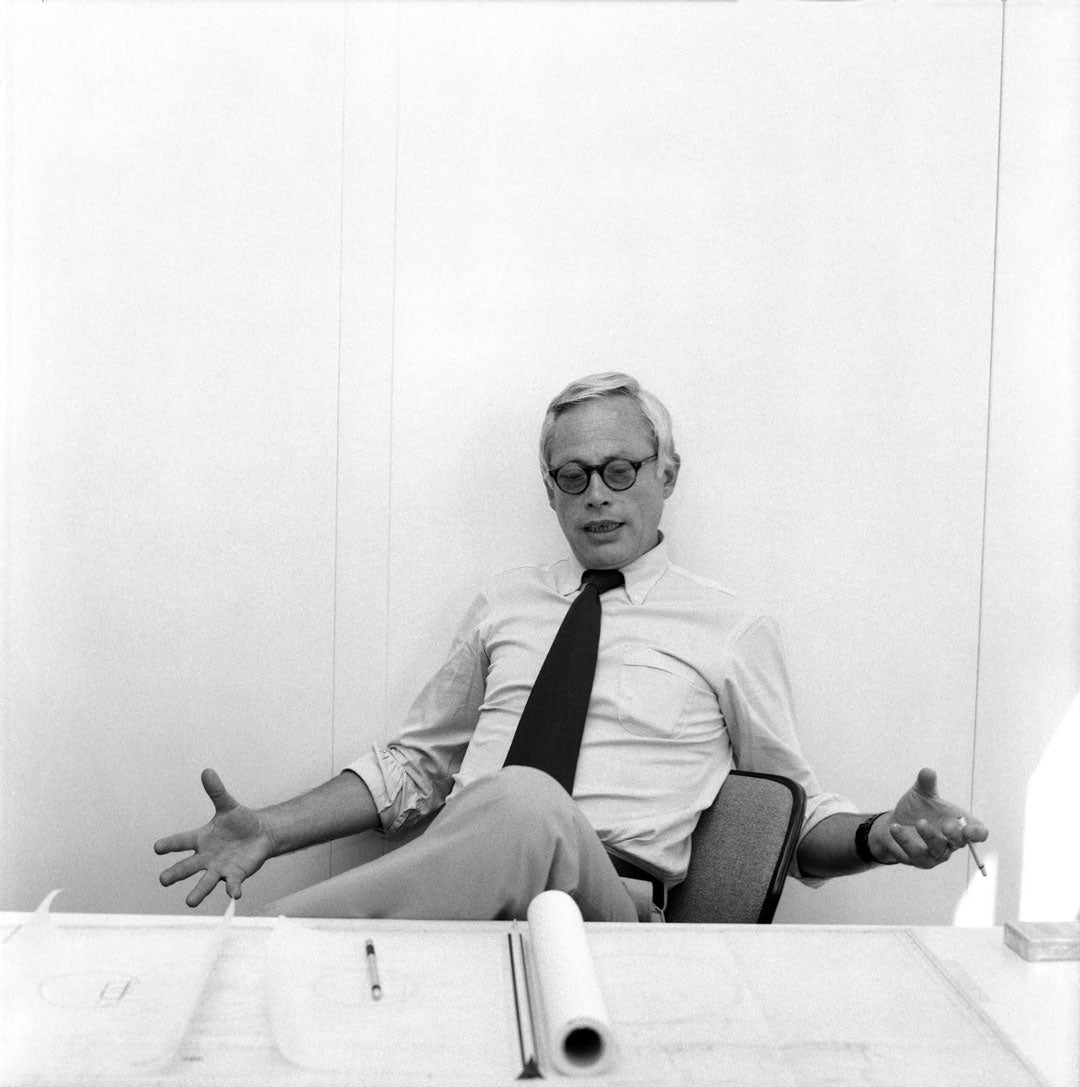 Dieter Rams sittign back in his chair wearing round black glasses