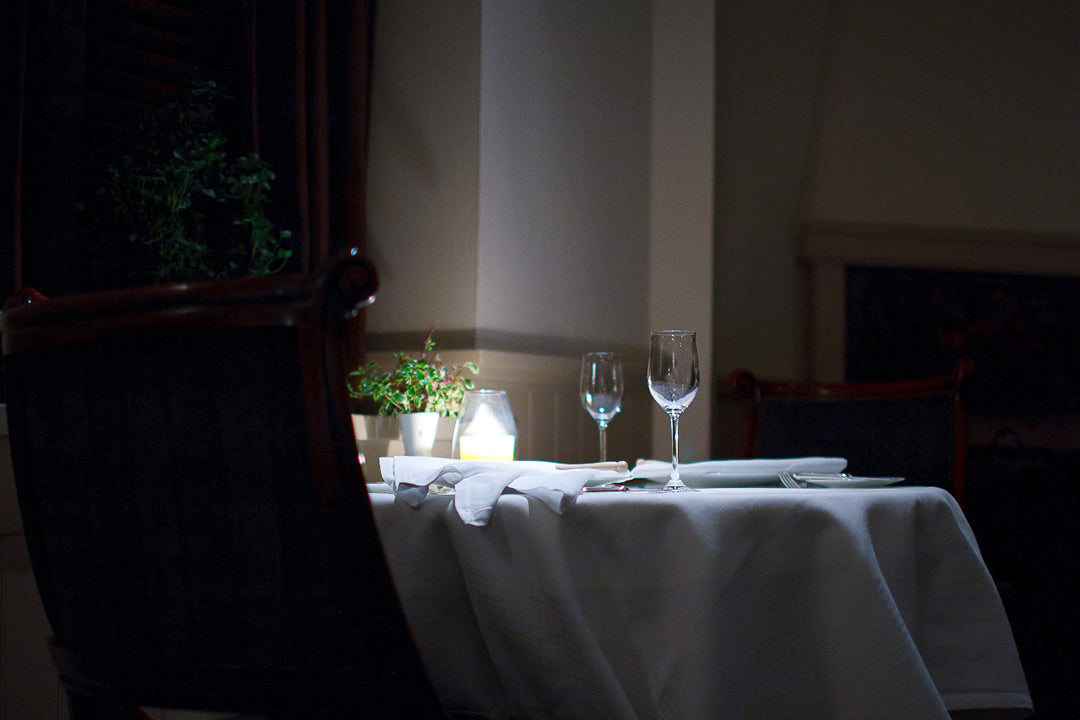 Dimly lit restaurant scene with white table cloth wine glasses plates and cutlery