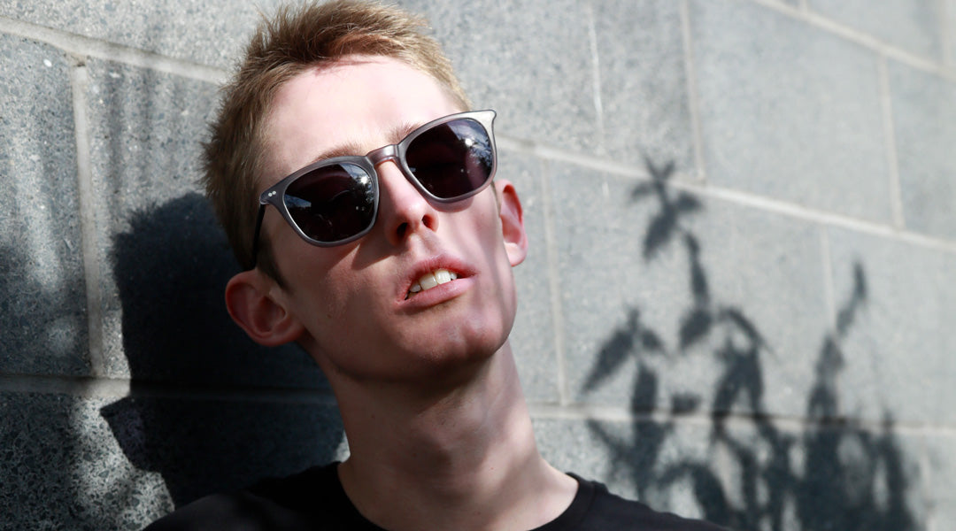 Fair haired young man wearing grey pair of sunglasses and dark T shirt