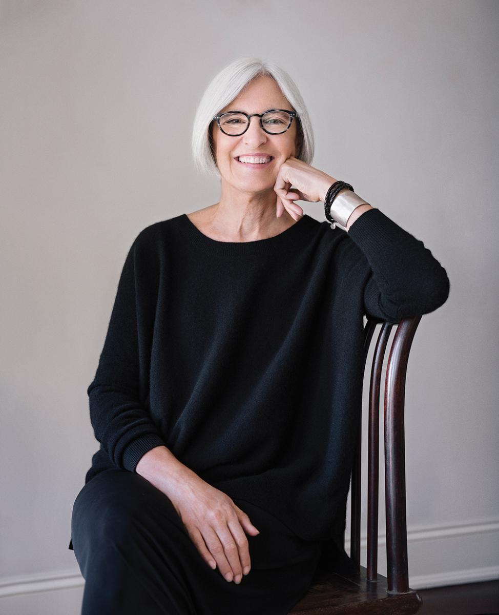Fashion designer Eileen Fisher sitting wearing dark clothes and speckled frame glasses
