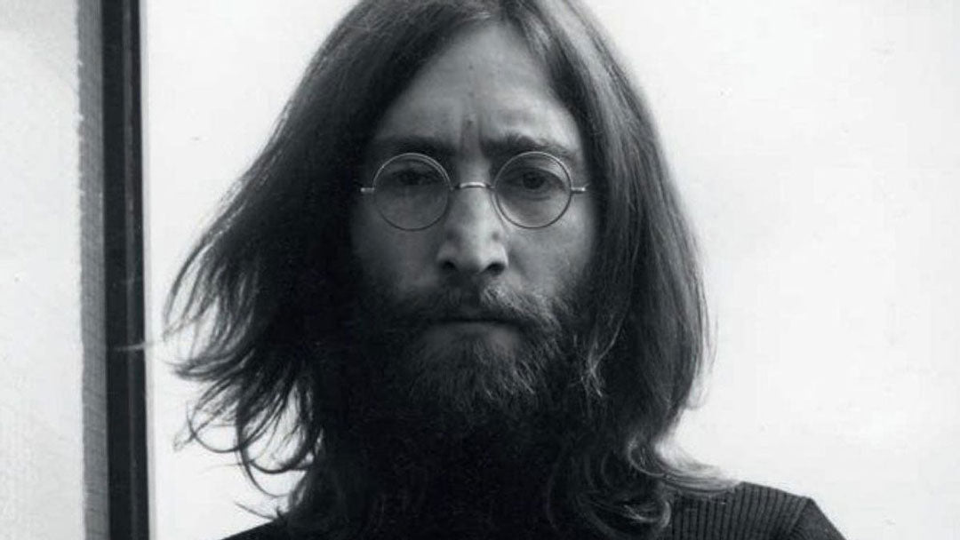 Front portrait view of John Lennon straing at viewer