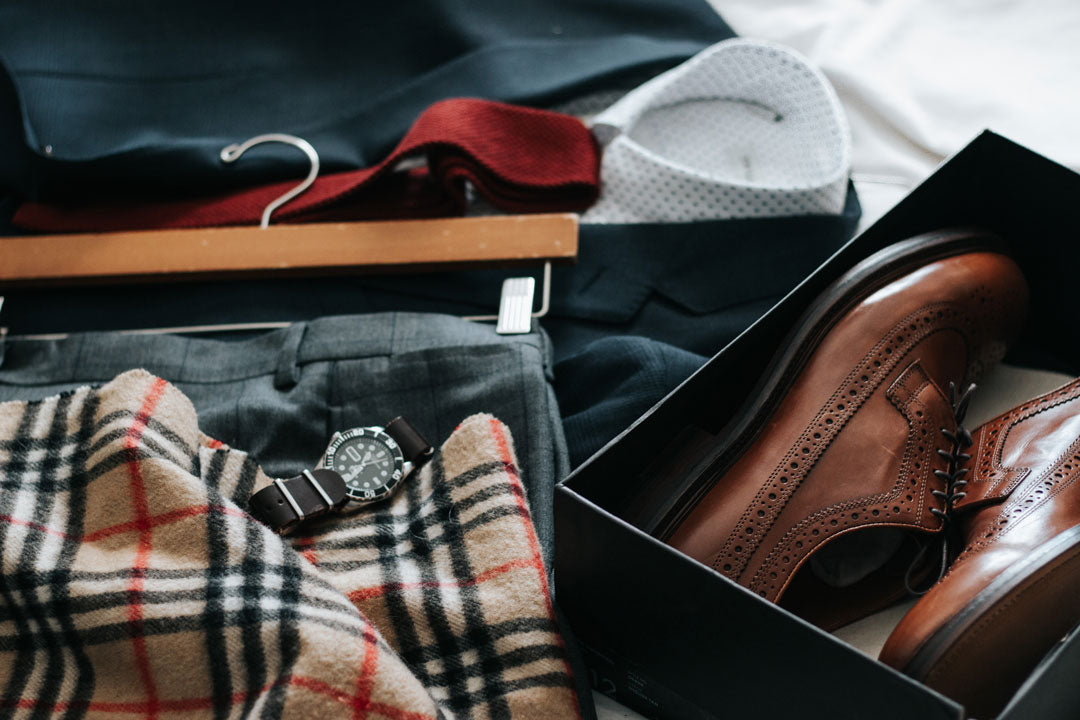 Gentleman's clothes shoes and accessories laid out on a bed