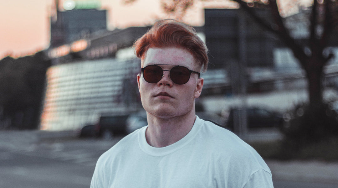 Ginger haired man wearing a white Tshirt and black aviator sunglasses