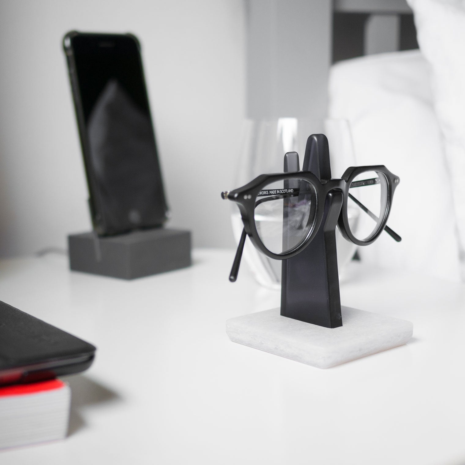 Glasses frame resting on grey spectacle stand in bedroom