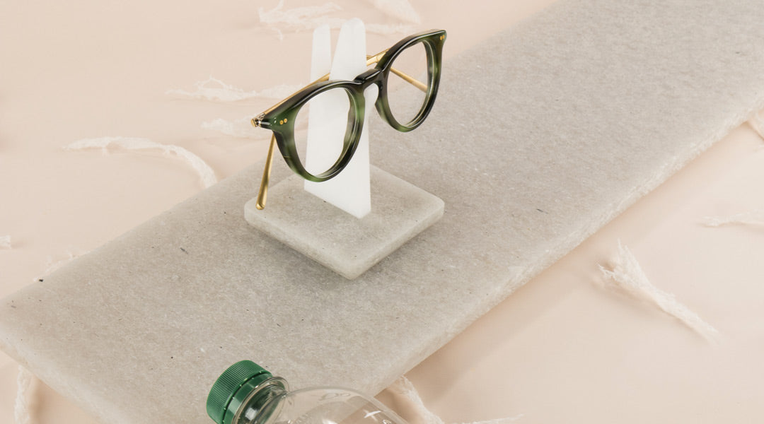 Green glasses resting on an upright eyeglass holder