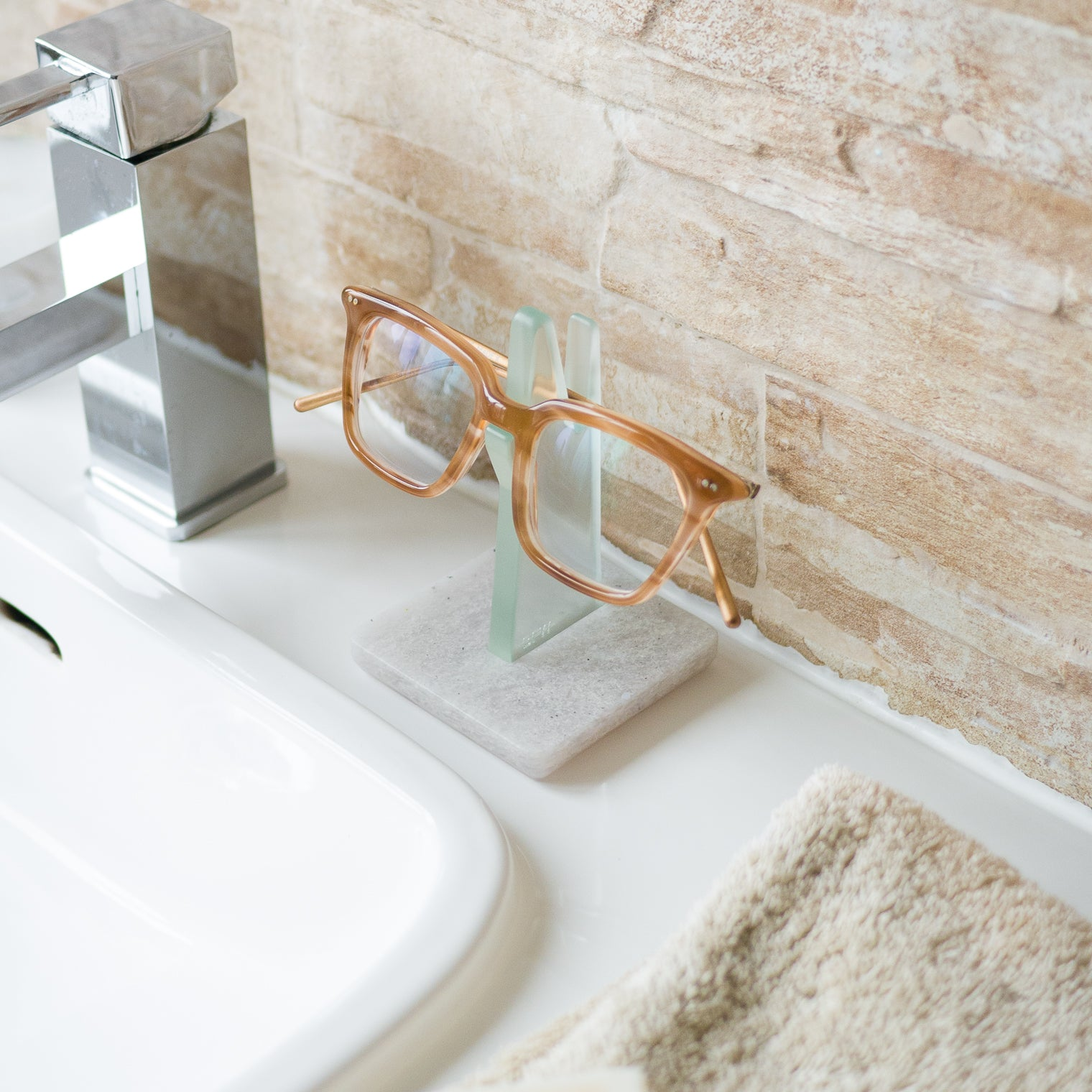 Green spectacle holder in bathroom holding glasses