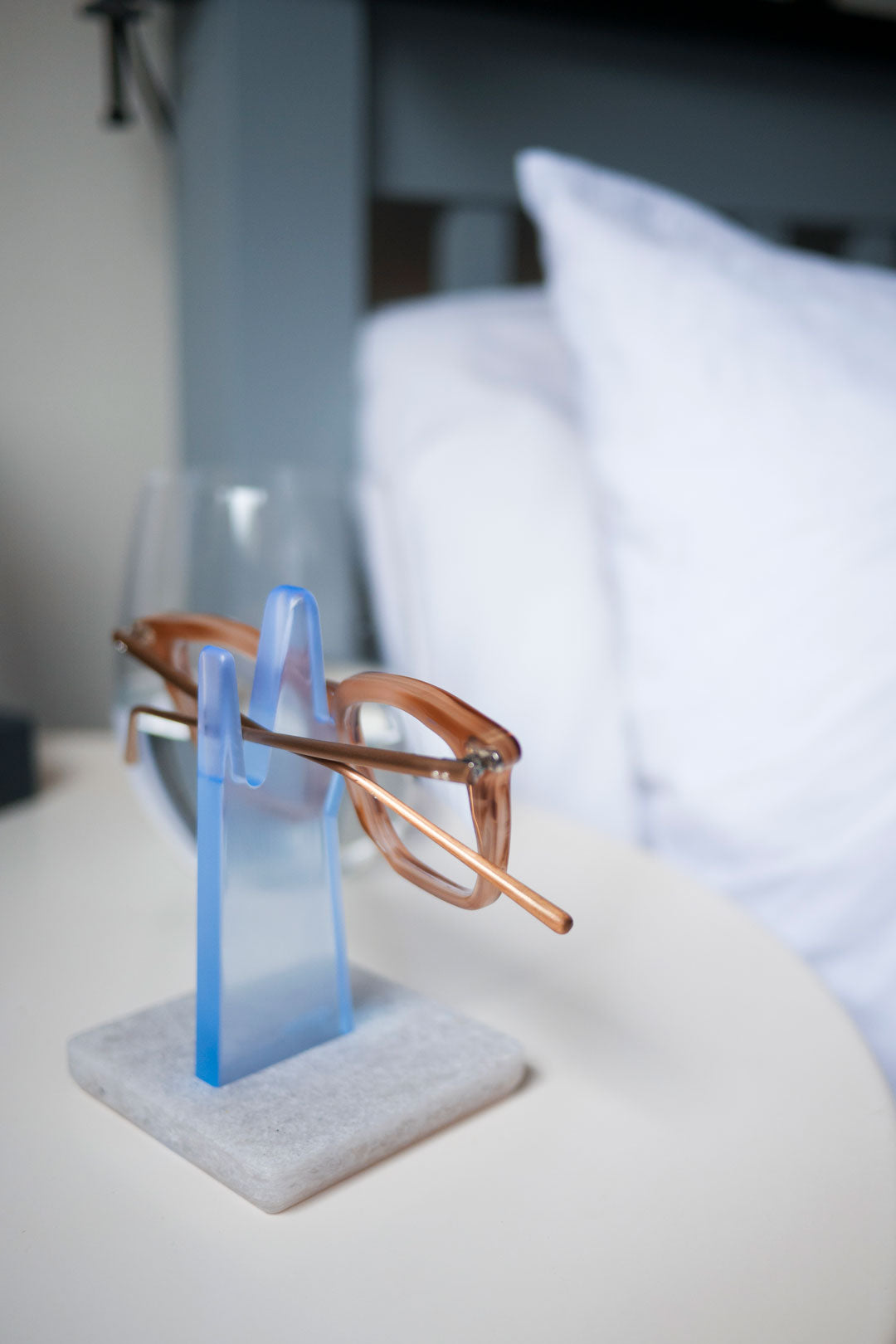 Grey and blue spectacle holder on bedside table