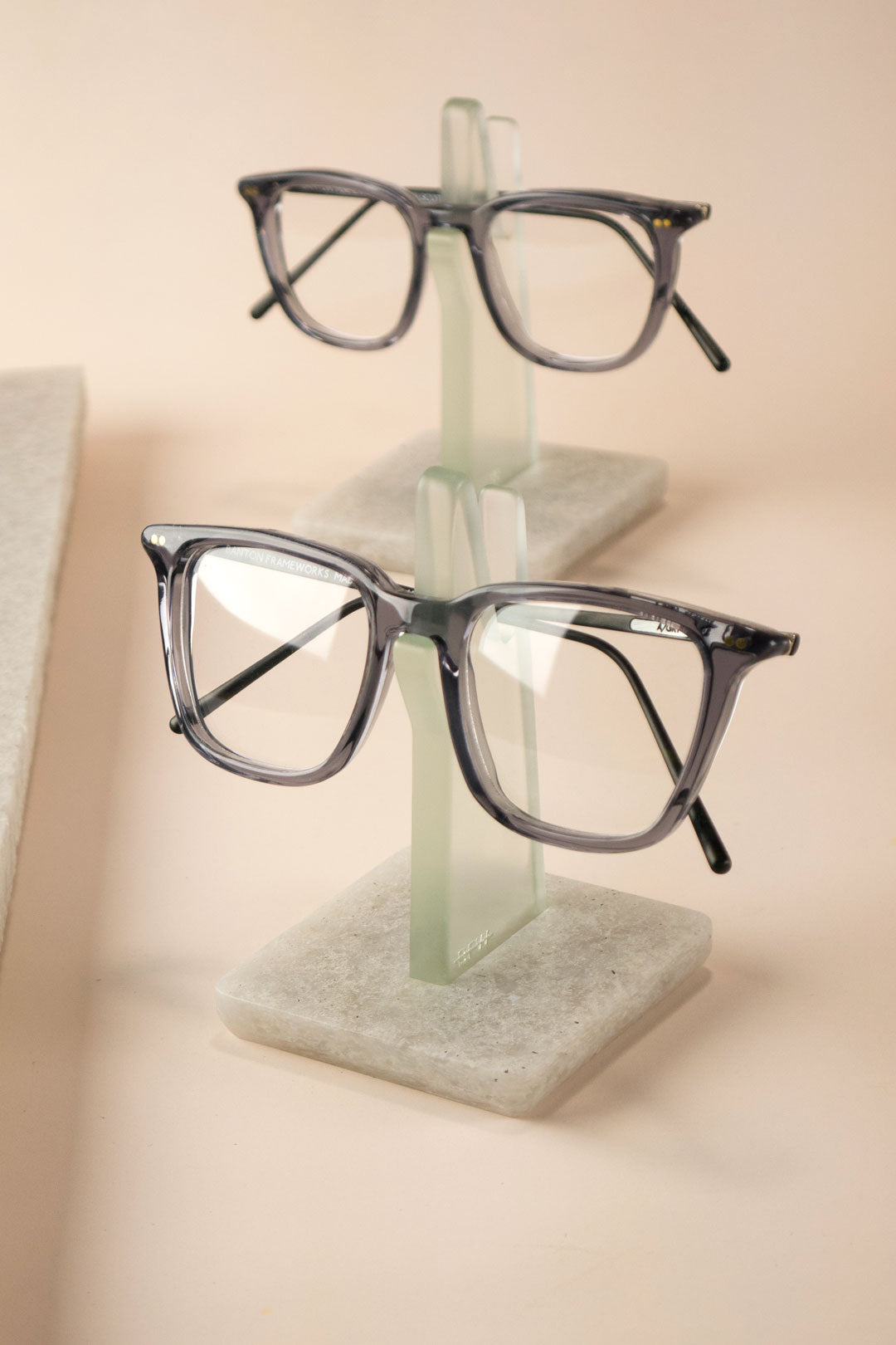 Grey glasses frames both placed on spectacle stands on pink background