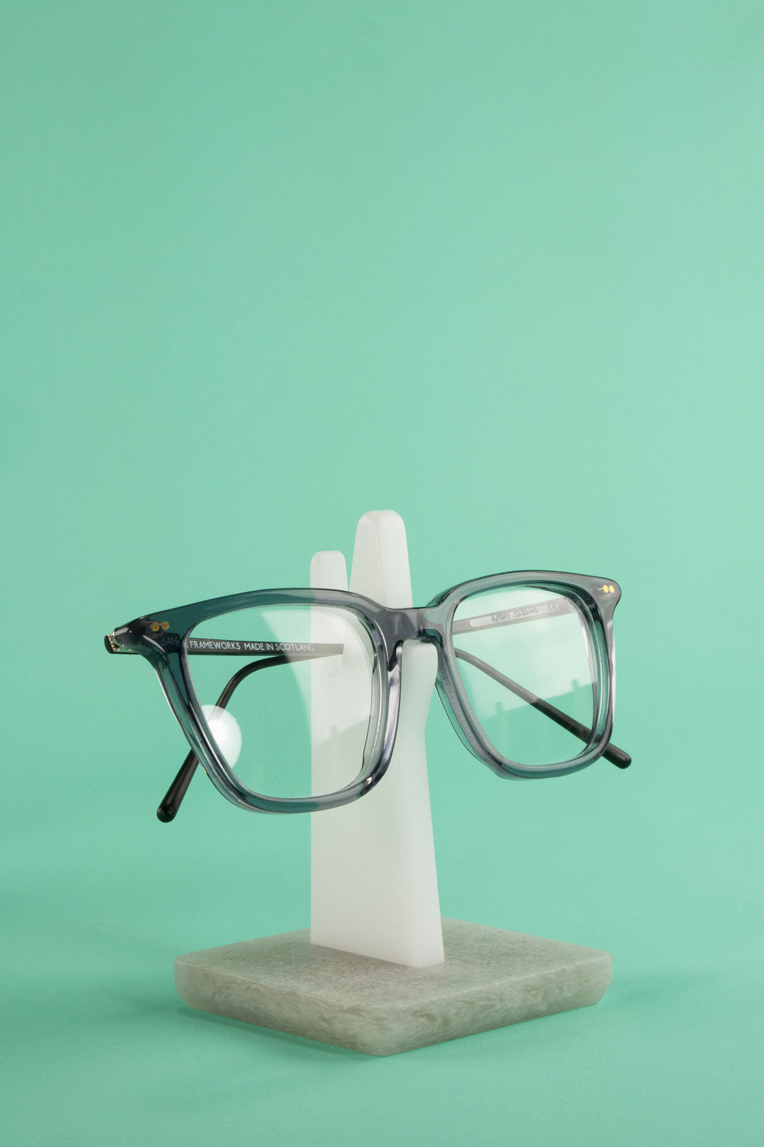 Grey glasses perched on white glasses stand in front of teal background