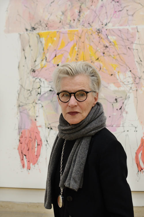 Grey haired lady standing in an art gallery wearing glasses and a grey scarf looking at the viewer