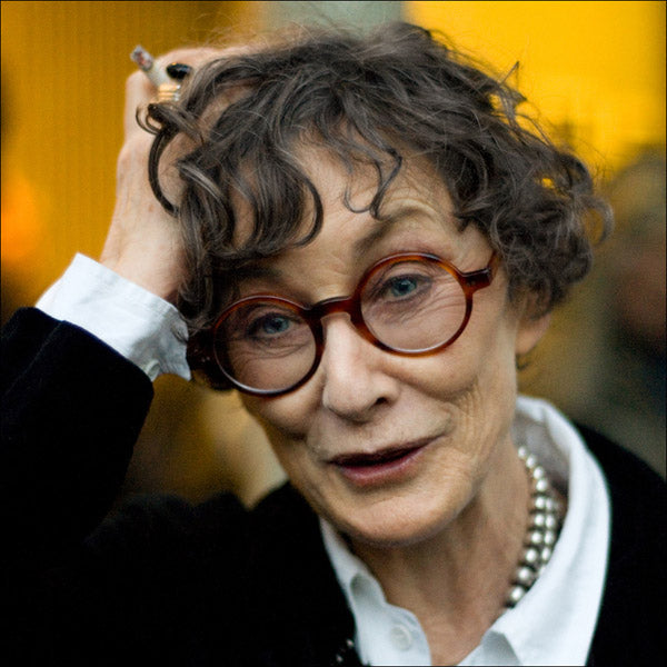 Grey haired lady with round amber glasses frame with one hand on her head holding a cigarette