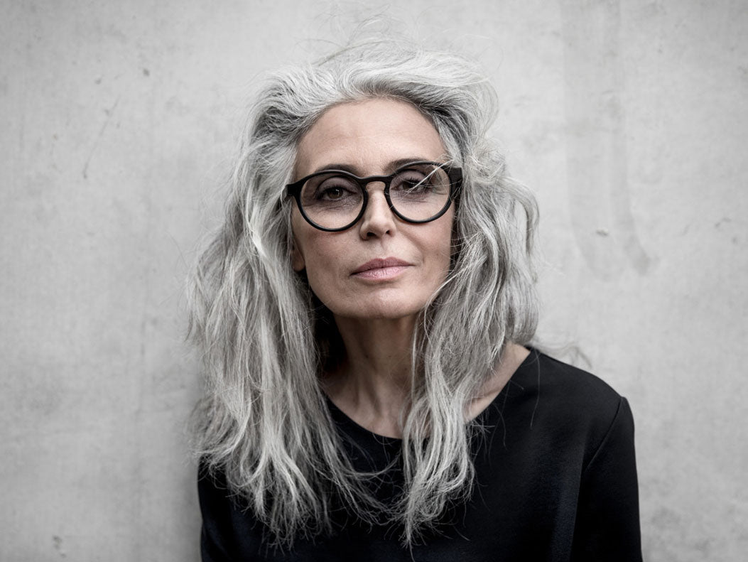 Grey haired woman wearing round black glasses