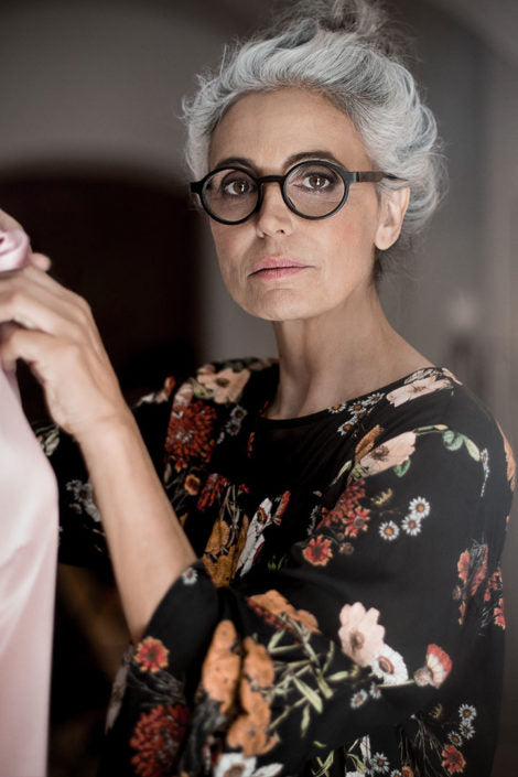 Grey haired woman with floral blouse and eyeglasses looking at viewer slightly side on