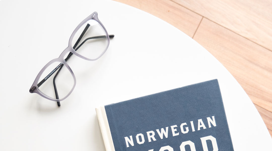 Grey reading glasses on circular white table beside a blue bound book