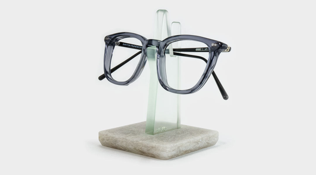 Grey spectacles resting on green and grey spectacle holder