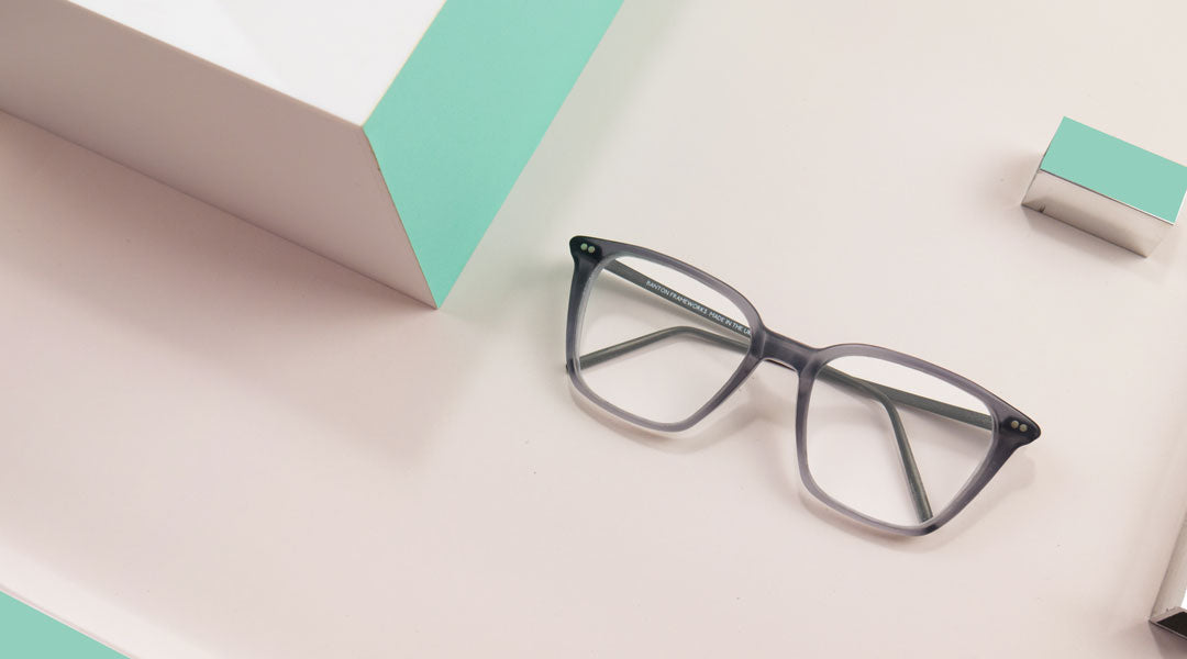 Grey varifocal glasses frame sitting on pink paper