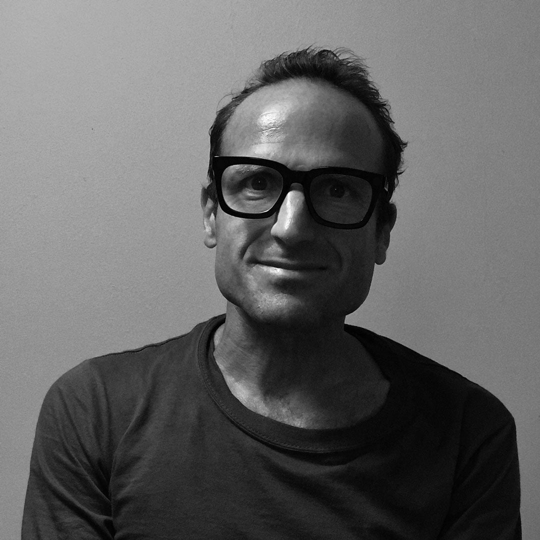 Greyscale image of Piers Taylor wearing black acetate architect glasses