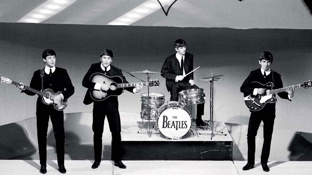 Greyscale image of the four band members of The Beatles
